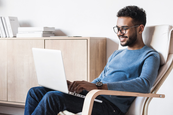 young adult man smiling at laptop